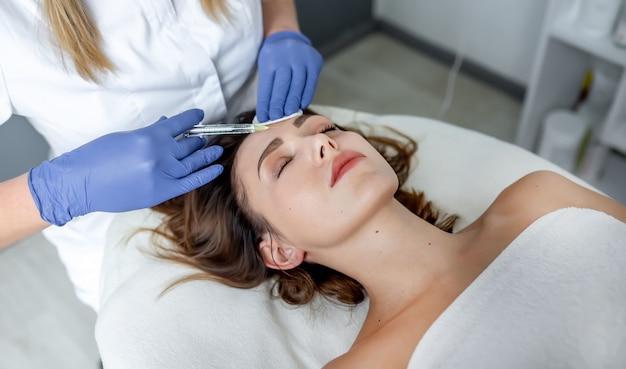 Mädchen kosmetikerin macht injektionen auf die lippen und das gesicht einer schönen frau in einem kosmetischen keil. kosmetikkonzept.