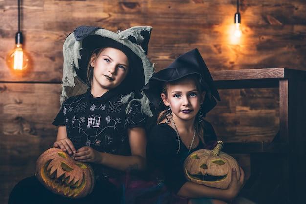 Mädchen kostüme hexen mit kürbissen und leckereien in der halloween auf holzlandschaft