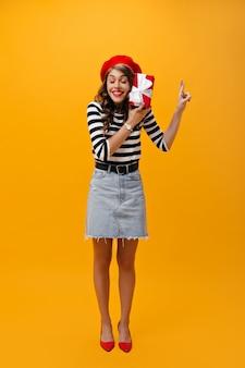 Mädchen kreuzt finger und hält geschenkbox auf orange hintergrund. coole frau in baskenmütze, jeansrock, gestreiftem hemd und roten absätzen posiert.