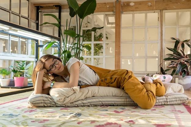 Mädchen künstler innenarchitekt gärtner rest auf dem boden im vintage-studio mit alten fenstern und pflanzen
