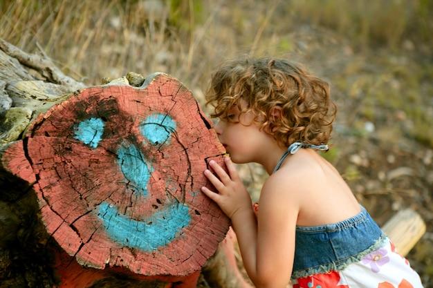 Mädchen küssen einen geschnittenen stamm mit glücklichem gesichtsabgehobenem betrag