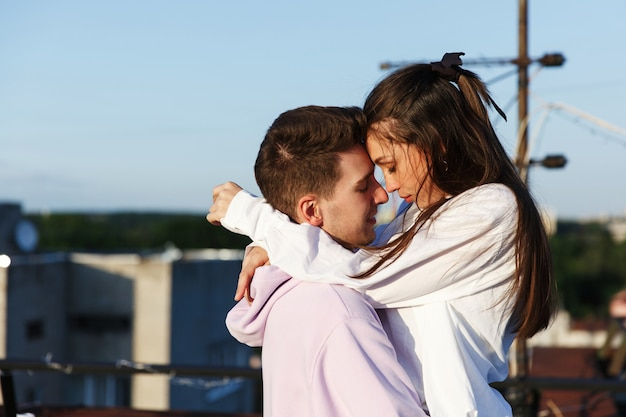 Mädchen küsst ihren mann, der auf dem dach steht und den sonnenuntergang überwacht