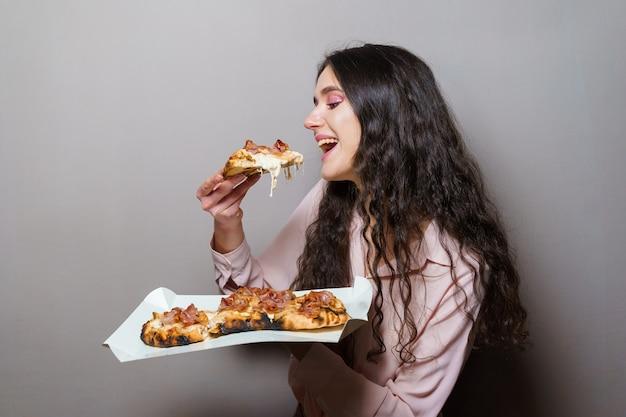 Mädchen kurier essen pinsa pizza romana gourmet italienische küche. halten traditionelles scrocchiarella-gericht. pinsa mit fleisch, rucola, oliven, käse.