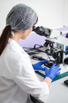 Mädchen labortechniker arbeitet an einem mikroskop in einem weißen schrank.