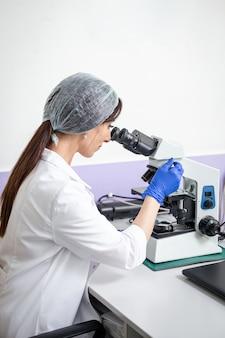 Mädchen labortechniker arbeitet an einem mikroskop.