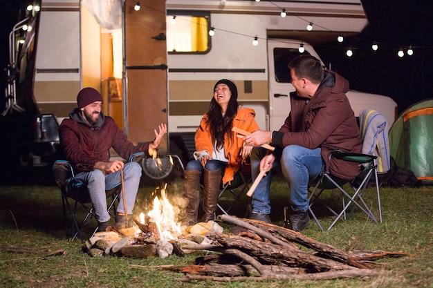 Mädchen lacht hart, nachdem ihre freunde einen witz am lagerfeuer mit retro-wohnmobil im hintergrund erzählt haben.