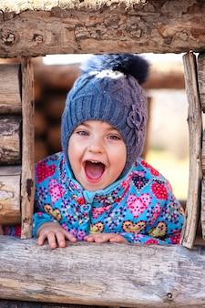 Mädchen lacht und spielt in einem holzhaus