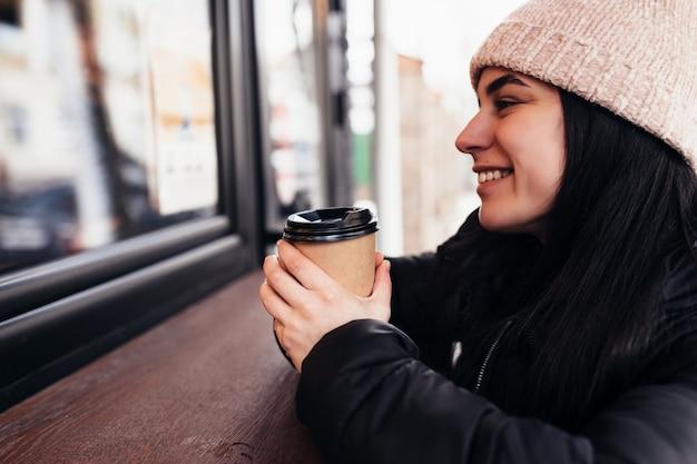 Mädchen lächelnd, hält pappbecher kaffee in der hand nahe café. unscharfer hintergrund. hochwertiges foto