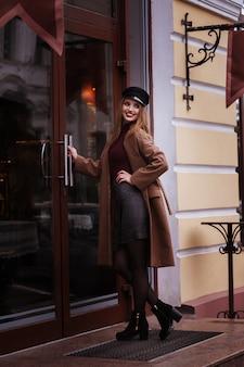 Mädchen lächelt im braunen herbstmantel und öffnet die tür