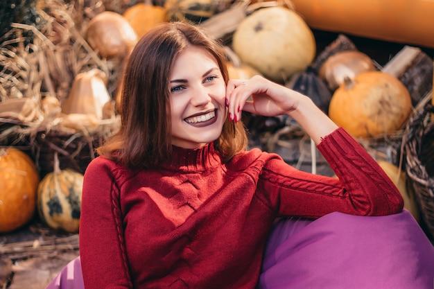 Mädchen lächelt im herbst auf dem hintergrund der kürbisse