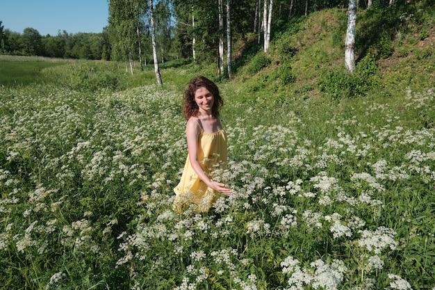 Mädchen lächelt, mädchen ist umgeben von weißen blumen und birken. wiesenblumen.