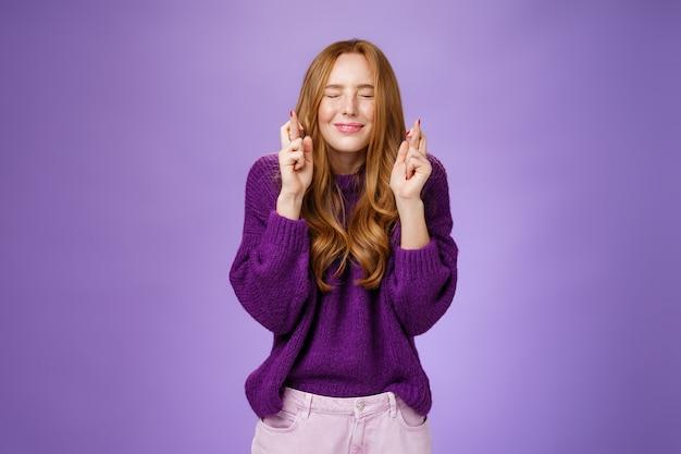 Mädchen lässt sehnsüchtigen traum wahr werden. attraktive hoffnungsvolle und positive junge rothaarige frau in lila pullover schließen augen und lächeln als kreuzfinger für viel glück, beten und antizipieren wunder.