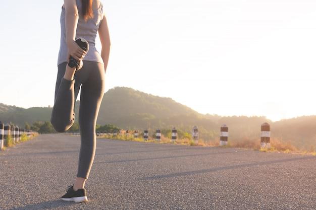 Mädchen läufer vor dem laufen auf der straße aufwärmen