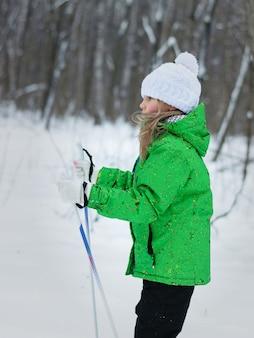 Mädchen läuft auf skiern im wald im profil