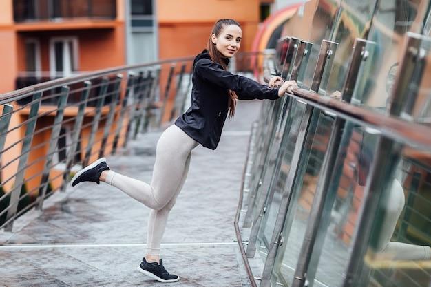Mädchen läuft im sommer in der stadt, auf dem morgenlauf. treppe hintergrund. kleidung leggings top.