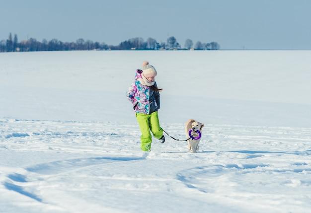 Mädchen läuft mit hund im schnee