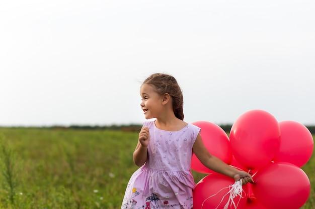 Mädchen läuft mit roten luftballons im sommer in der natur