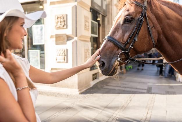 Mädchen legt pferde im stadtzentrum