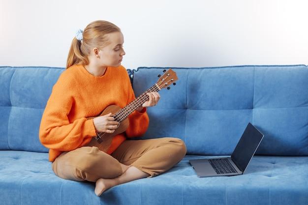 Mädchen lernt aus der ferne ukulele spielen