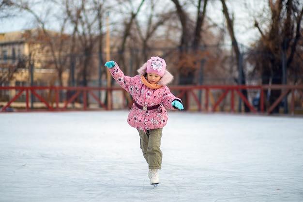 Mädchen lernt im winter auf einer eisbahn auf einer straße schlittschuh zu laufen