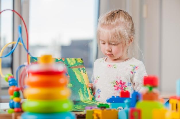 Mädchen lesen buch in kindertagesstätte