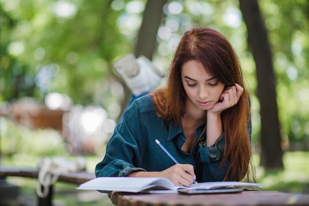Mädchen liegt auf dem tisch im park schriftlich