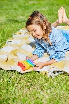 Mädchen liegt auf einer decke auf gras im freien und spielt pop es, kinderhände spielen blasen eines regenbogen-entstressungsspielzeugs, zappelspielzeug im hinterhof des hauses an einem sonnigen sommertag, sommerurlaub.