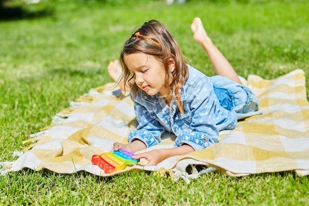 Mädchen liegt auf einer decke auf gras im freien und spielt pop it, kinderhände spielen mit buntem pop it, zappelspielzeug im hinterhof des hauses an einem sonnigen sommertag, sommerurlaub.
