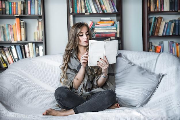 Mädchen liest buch auf sofa