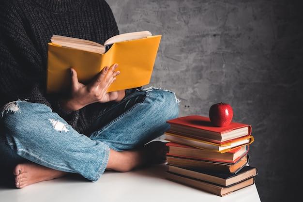 Mädchen liest bücher, studiert, entwickelt auf einem weißen tisch und einem grauen hintergrund.