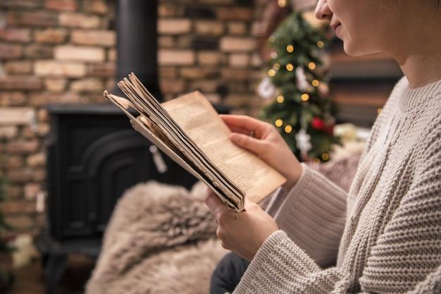 Mädchen liest ein buch in einer gemütlichen häuslichen atmosphäre in der nähe des kamins, nahaufnahme