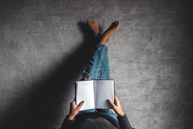 Mädchen liest ein buch mit seinen beinen zur wand, grauem hintergrund, bildung, hobby, entwicklung.