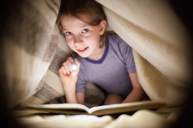Mädchen liest ein buch unter einer decke mit einer taschenlampe in einem dunklen raum nachts