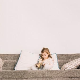 Mädchen liest magazin auf der couch