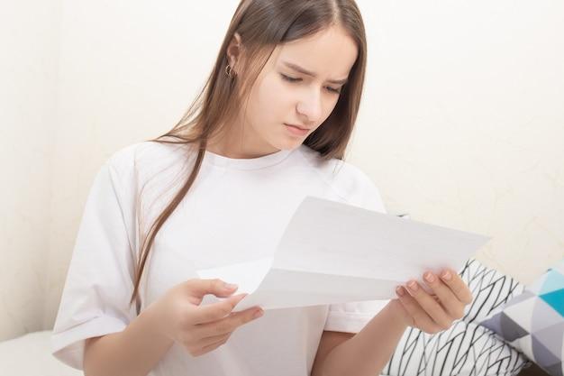 Mädchen liest zu hause einen brief auf einem blatt papier
