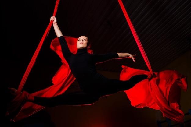 Mädchen-luftakrobat, der schnur auf luftleinwänden tut. akrobatik in der luft