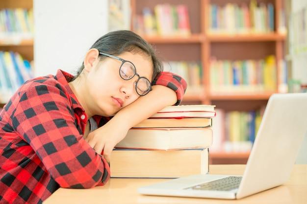 Mädchen machen ein nickerchen, während sie bücher lesen