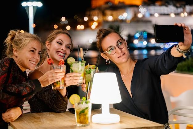 Mädchen machen ein selfie, während sie auf einer terrasse sitzen und nachts cocktails trinken