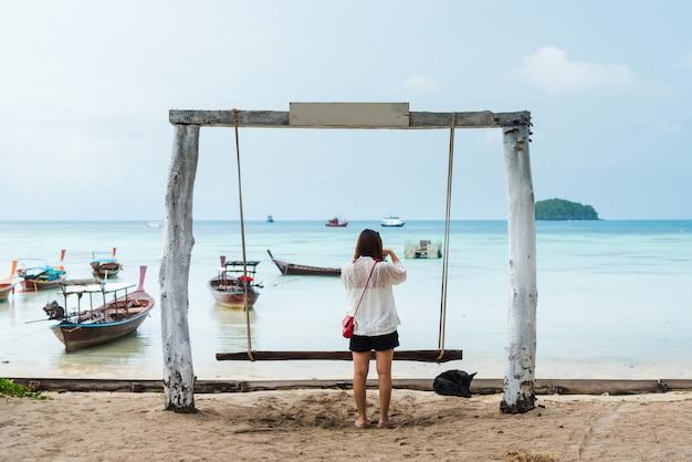 Mädchen machen foto auf der schaukel am tropischen strand