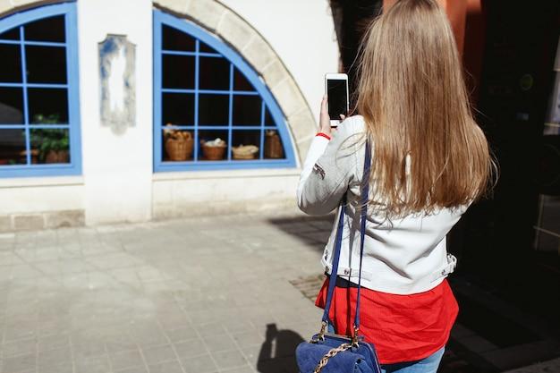 Mädchen macht ein foto eines blauen fensters an ihrem telefon