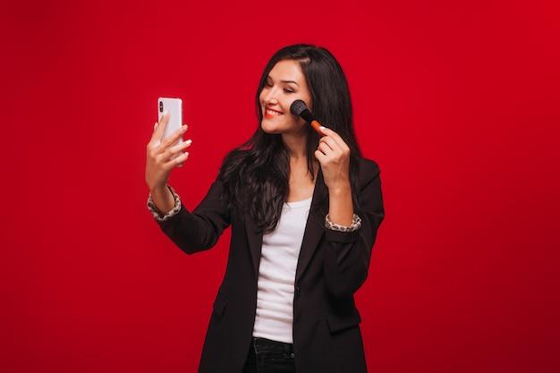 Mädchen macht ein make-up, das das kamerahandy betrachtet