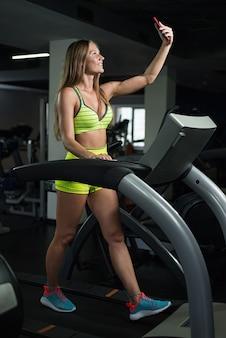Mädchen macht ein selfie im fitnessstudio, frau wird auf dem laufband fotografiert