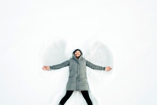 Mädchen macht einen schneeengel im weißen schnee.