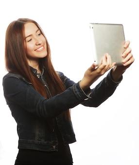 Mädchen macht selfie mit digitalem tablet, isoliert auf weißem hintergrund