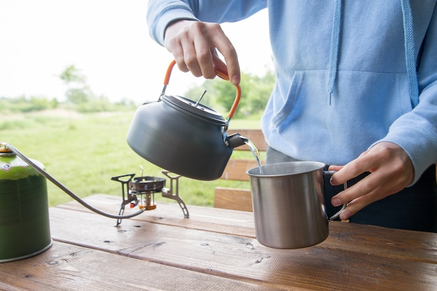 Mädchen macht tee und kaffee auf dem campingplatz oder auf einem picknick