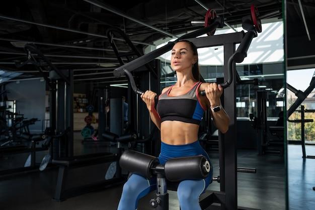 Mädchen macht übungen für die rückenmuskulatur an kraftgeräten im fitnessstudio
