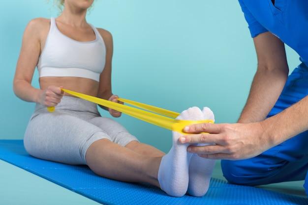 Mädchen macht übungen mit einem physiotherapeuten. cyan wand