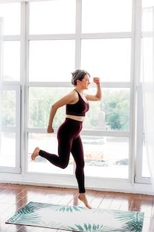 Mädchen macht übungen, stretching, yoga, in der nähe des fensters, yoga-anzug, körper, schlankheit und gesundheit