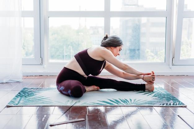 Mädchen macht übungen, stretching, yoga, teppich in der nähe des fensters, yoga-anzug, körper, schlankheit und gesundheit