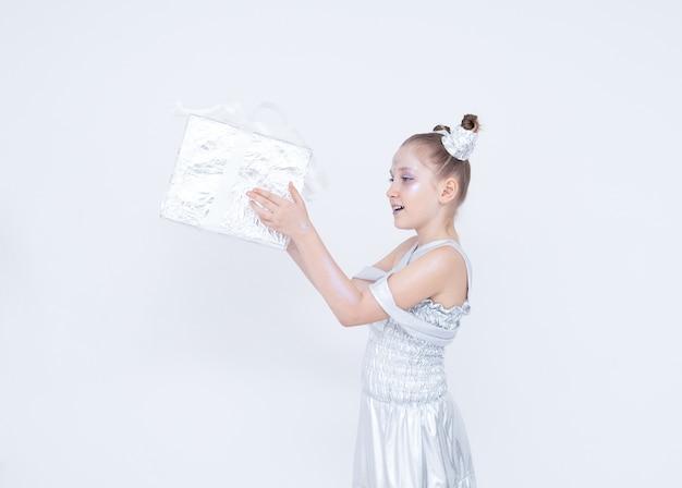 Mädchen mädchen mit schwänzen hörner in einem silbernen kleid hält eine geschenkbox